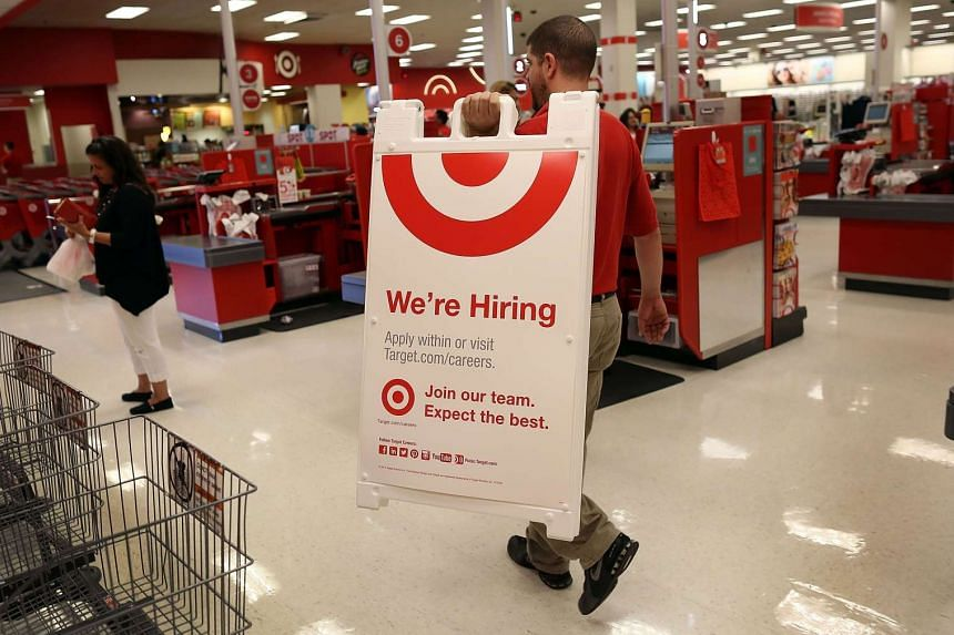A Target store manager preparing to put up a hiring sign outside an outlet in Miami on Sept 4, 2015.