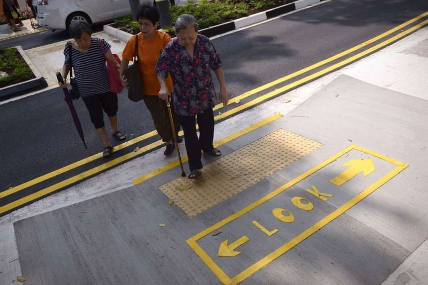 "Elderly women crossing a road with the ""look"" ground markings at the Silver Zone in Bukit Merah View."