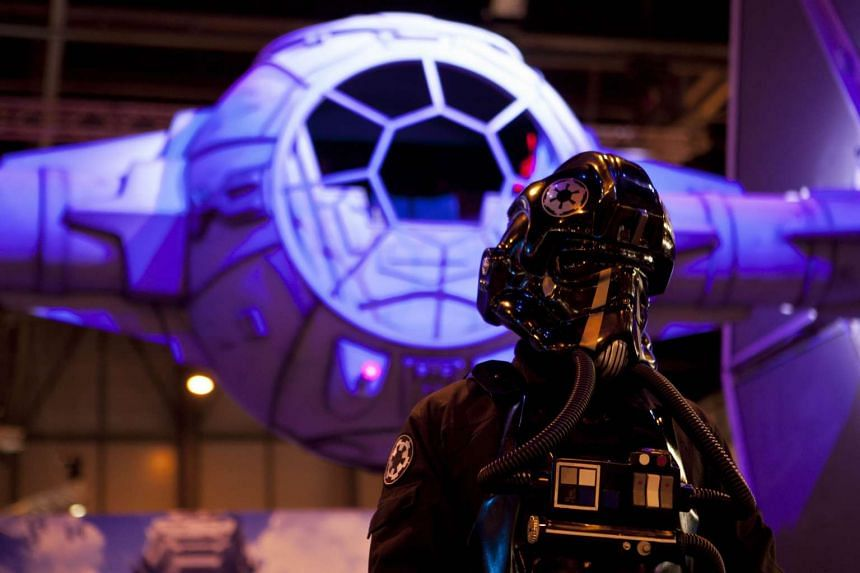 An actor posing by a model of a Star Wars TIE fighter during the Madrid Games Week on Oct 1, 2015.