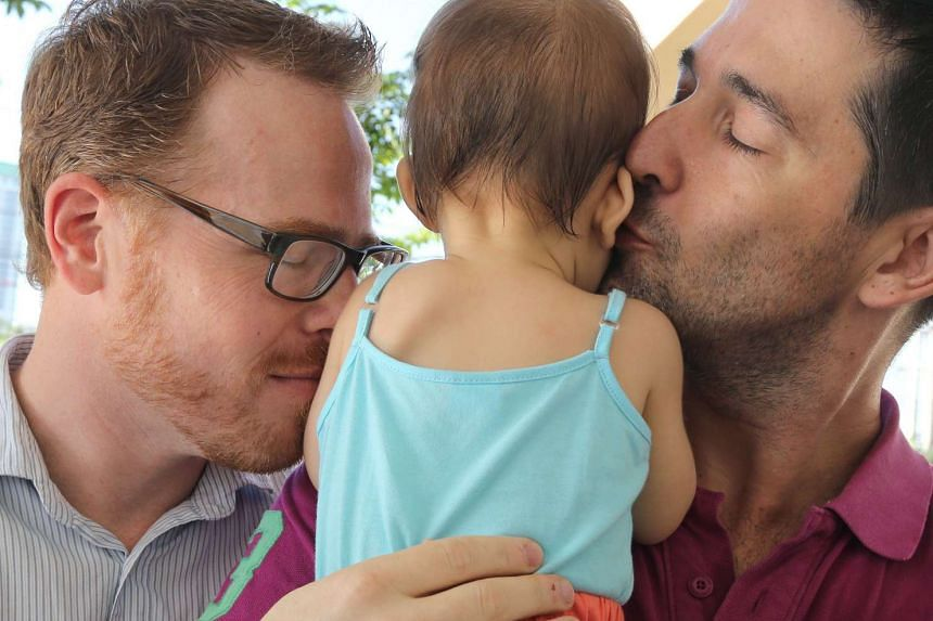 Gordon Lake (left) and Manuel Santos (right) with nine-month-old Carmen at the Central Juvenile and Family Court in Bangkok on Oct 30, 2015.