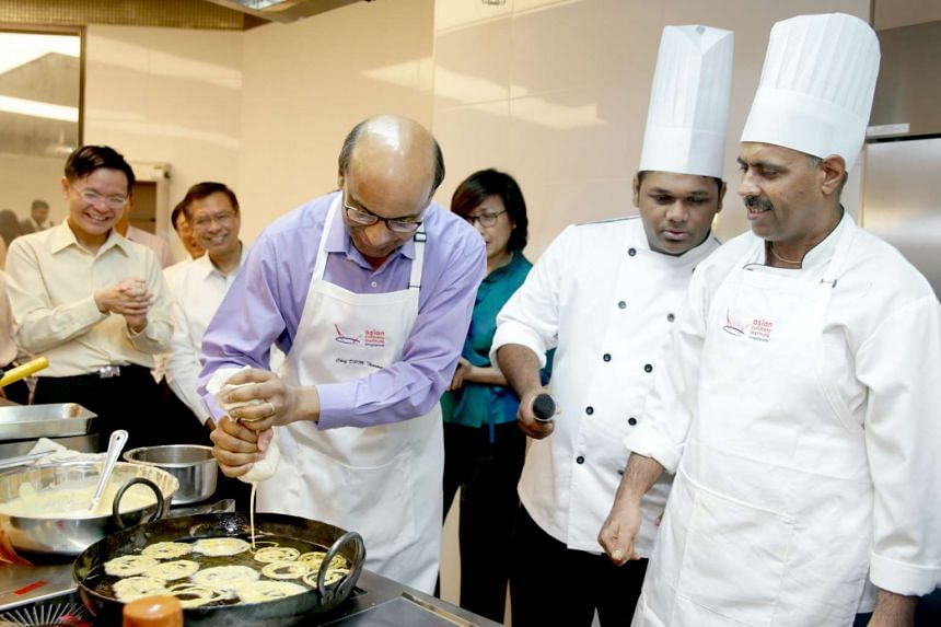 Deputy Prime Minister Tharman Shanmugaratnam (centre) trying his hand at making jileb during the signing of the MOU.