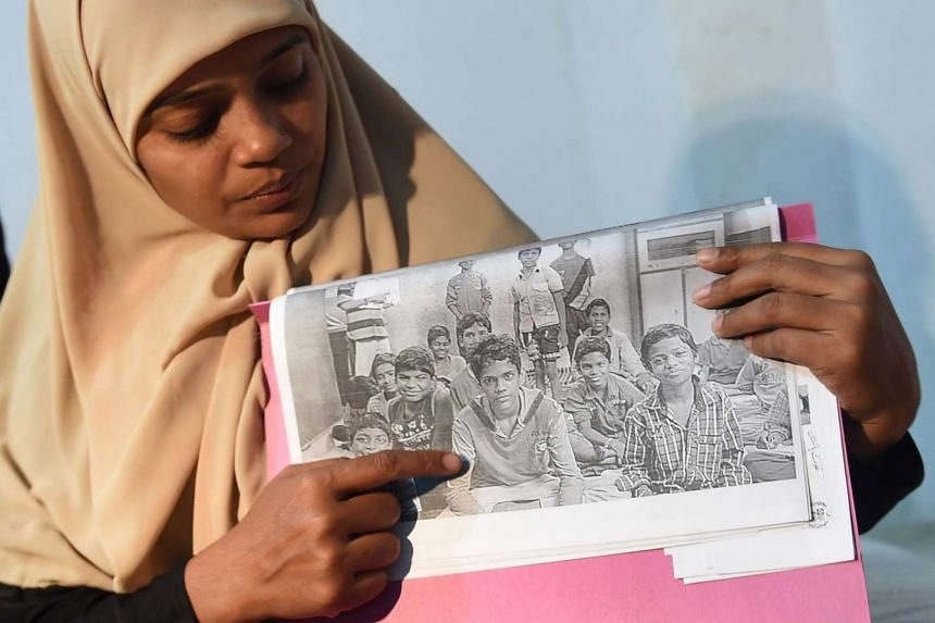 Razia Begum displaying a picture of her son, Mohammad Ramazan, during an interview in Karachi on Oct 30, 2015.