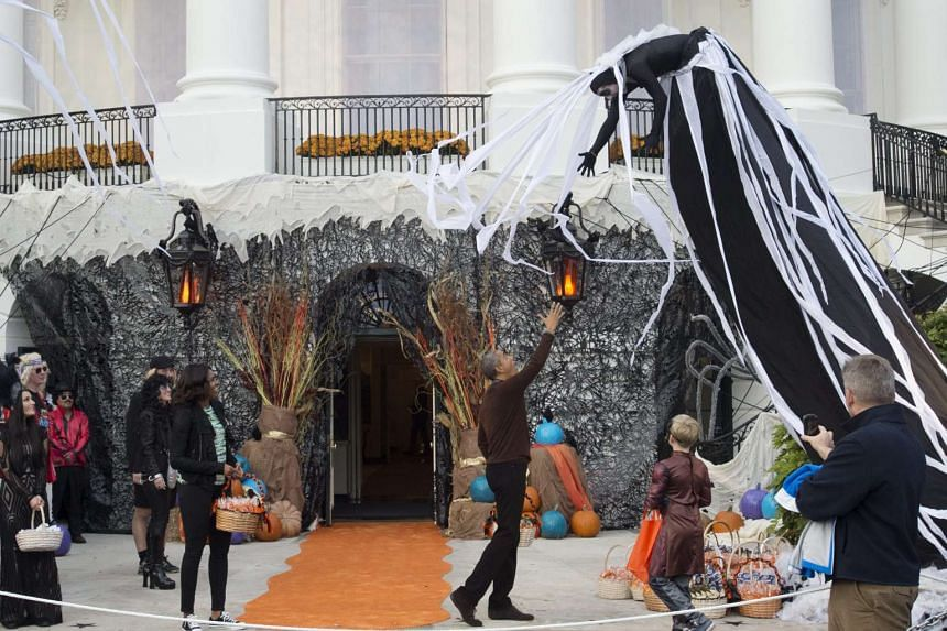 US President Barack Obama reaching up to a performer as First Lady Michelle Obama looks on; during a Halloween event at the White House in Washington, DC, USA, on Oct 30, 2015. President Obama and the First Lady welcomed local children and children o