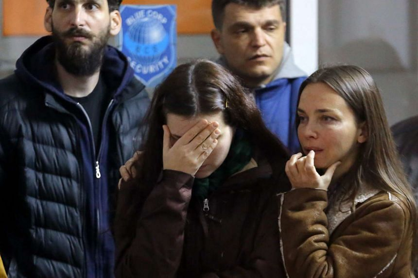 Romanian relatives of club explosion victims watch survivors being transferred in ambulances.