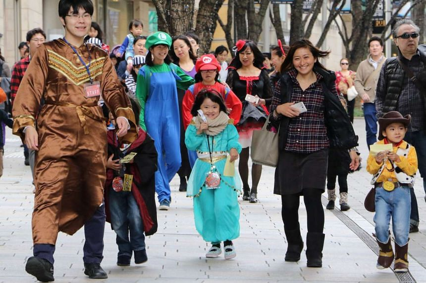 Children and their parents wear costumes as they take part in a Halloween parade in Tokyo on October 31, 2015.