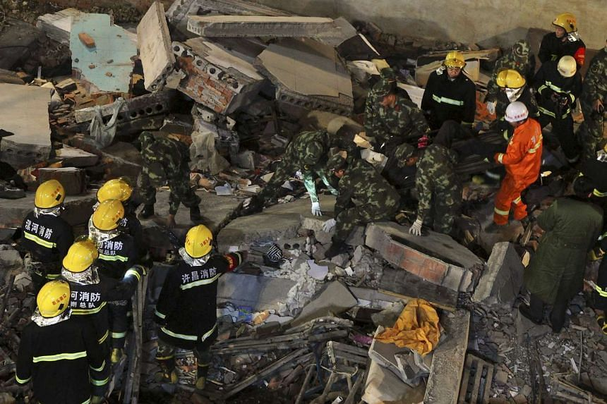 Rescuers search for survivors among debris after a residential building collapsed in Wuyang county, Henan province, China on Oct 30, 2015. At least 17 construction workers were killed after a two-storey old house collapsed during a renovation projec