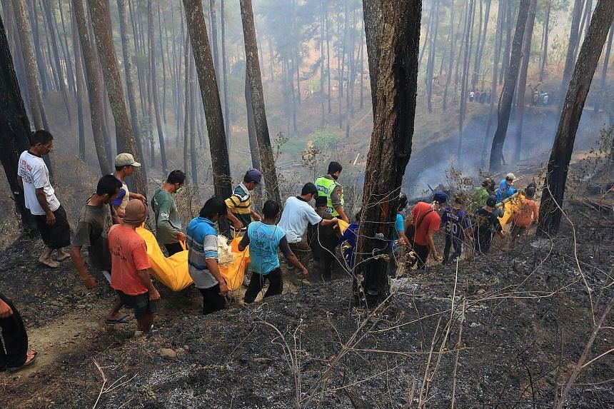 Indonesian villagers carrying the bodies of four people who were killed while trying to put out a forest fire in Ponorogo district in East Java on Thursday.