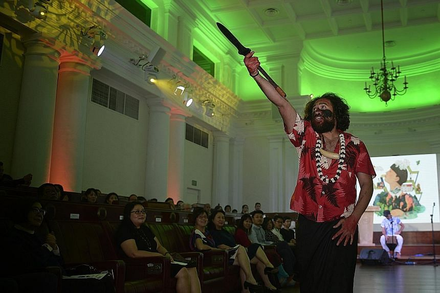 Performance poet Daren Kamali holding a Wau, a Fiji warrior weapon, during the Stories From Islands, Songs From Islanders II readings at The Arts House yesterday.
