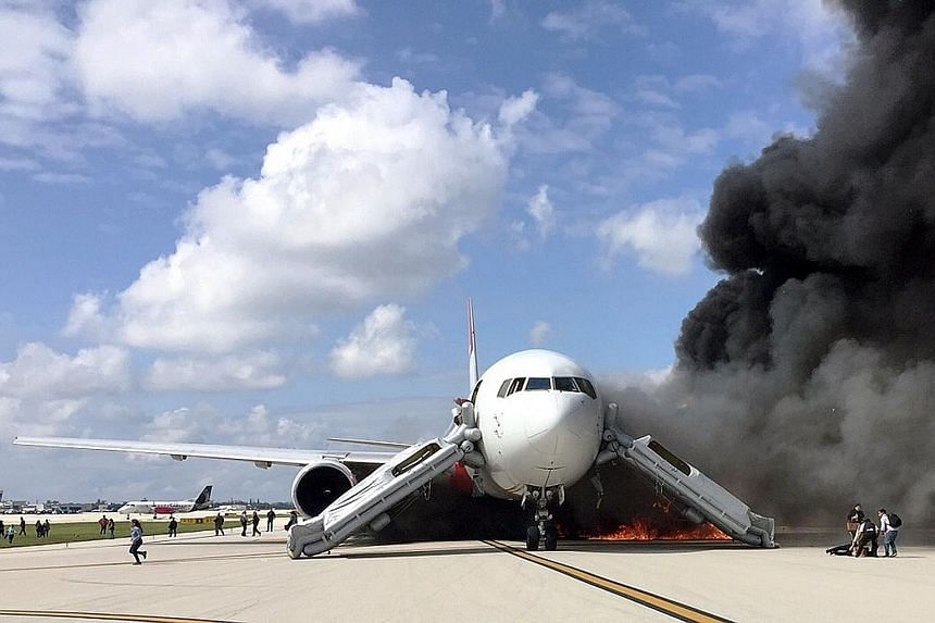 Black smoke billowing from the plane after an engine caught fire as it was taxiing for take-off on a runway at the Fort Lauderdale airport in Florida on Thursday. Officials said there were 101 people on board.