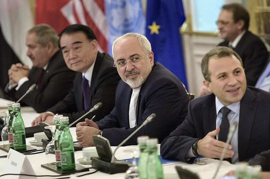 Iranian Foreign Minister Javad Zarif (second from right) and Chinese Vice-Foreign Minister Li Baodong (second from left) waiting with others before a meeting in Vienna to discuss solutions to the conflict in Syria.
