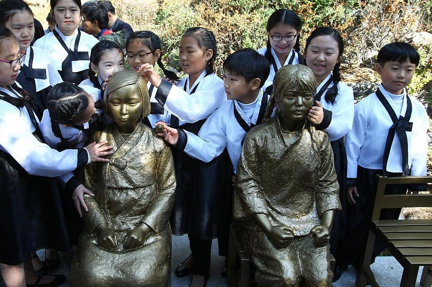 """Schoolchildren crowding around bronze statues depicting Korean and Chinese """"comfort women"""", who were forced into prostitution at Japanese wartime brothels, at a park in Seoul this week."""