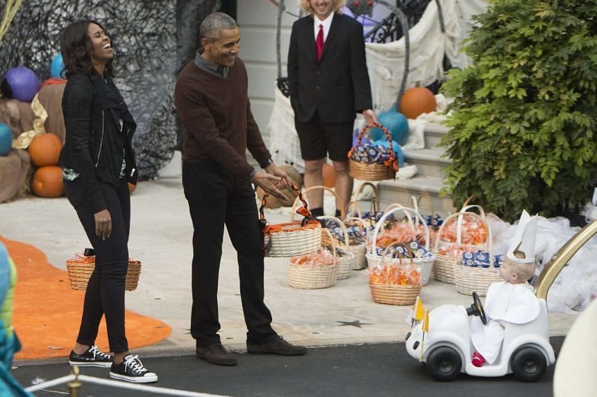 US President Barack Obama (second from left) and First Lady Michelle Obama (left) laughing at the sight of a child dressed as the Pope at a Halloween event at the White House on Oct 30, 2015. President Obama and the First Lady welcomed local children