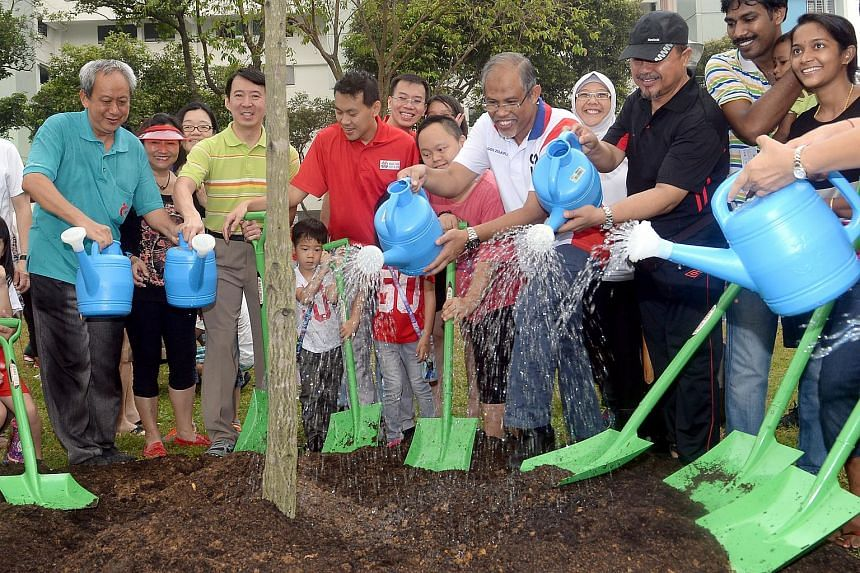 Mr Masagos Zulkifli (in white), Minister for Environment and Water Resources, planting the tembusu tree, with Tampines residents as part of the Clean and Green Campaign on Oct 25, 2015.