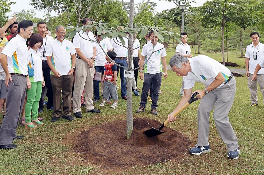 Prime Minister Lee Hsien Loong planting a Jelutong tree at Punggol Waterway Park with residents and other MPs, before launching the Clean And Green SG50 Carnival.