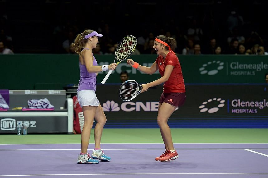 Martina Hingis (purple) and Sania Mirza celebrate their semi-finals victory in the WTA Finals.