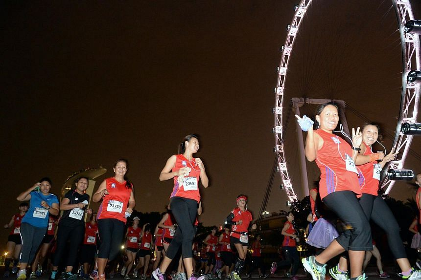Participants running past the Singapore Flyer just after the flag-off for the 21.1km event.
