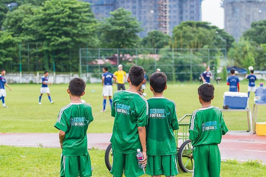 Boys from the Yangon Football Academy watching the senior team during morning training. Some football observers say that Myanmar is stumbling upon a golden generation, with its U-20 football team a surprise qualifier for the U-20 World Cup in New Zea