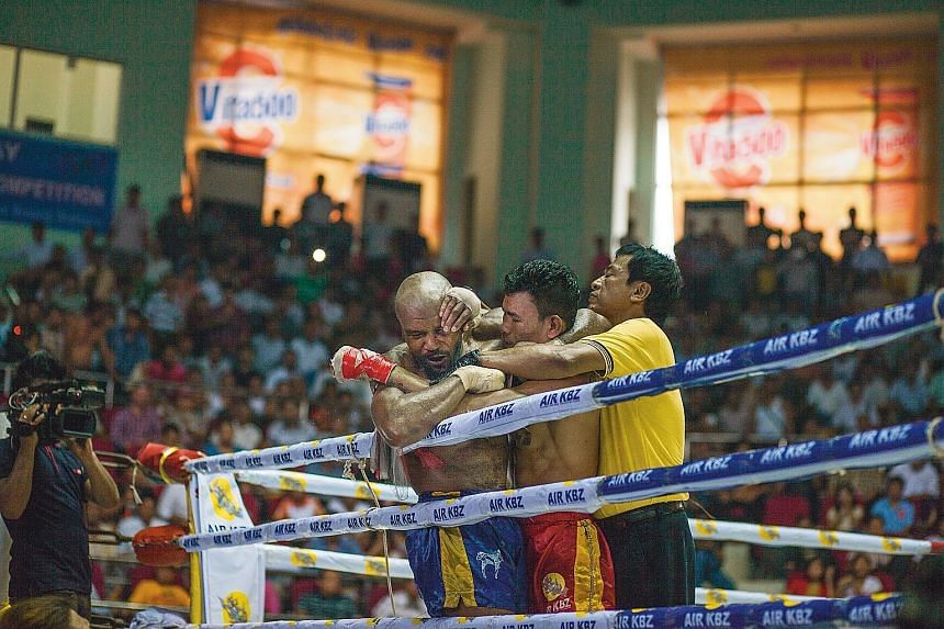 American Cyrus Washington, 33, battling Too Too, 23, of Myanmar, in a lethwei match at the Thein Phyu Stadium in July.
