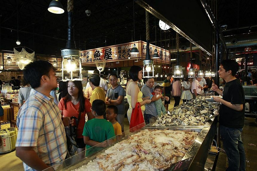 Customers checking out fresh seafood on sale at one of the stalls in PasarBella, a market located at The Grandstand.