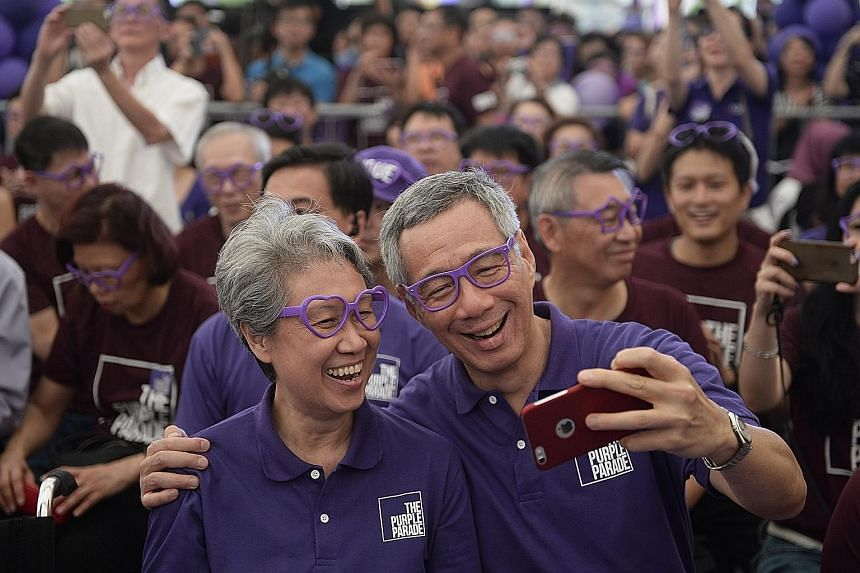 Donning purple spectacles, Prime Minister Lee Hsien Loong takes a selfie with his wife Ho Ching as they join participants at The Purple Parade held in Hong Lim Park. More than 7,000 people attended the event yesterday.