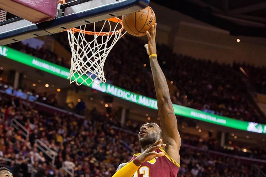 LeBron James of Cleveland going up for a basket against his former team Miami. The Cavaliers defeated the Heat 102-92 with James netting 29 points and Kevin Love weighing in with another 24.