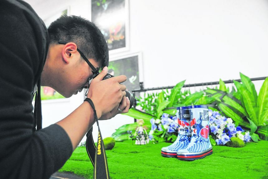At China's Zhejiang Agriculture and Forestry University yesterday, an undergraduate takes a photo of a pair of boots at a studio of an e-commerce firm. In preparation for Singles Day, which falls on Nov 11, e-commerce undergraduates are stocking up o