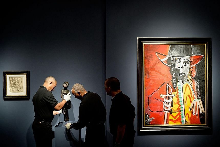 Workers making adjustments to the display of a sculptureduring a preview of an impressionist and modern art auction at Christie's in New York, on Friday. The auction house is expecting millions in sales.