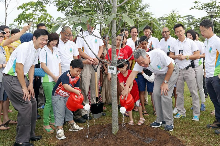 Prime Minister Lee Hsien Loong plants a jelutong tree at the Punggol Waterway Park. With him are (from left) Minister for National Development Lawrence Wong; Senior Minister of State for the Environment and Water Resources Amy Khor; Minister for the