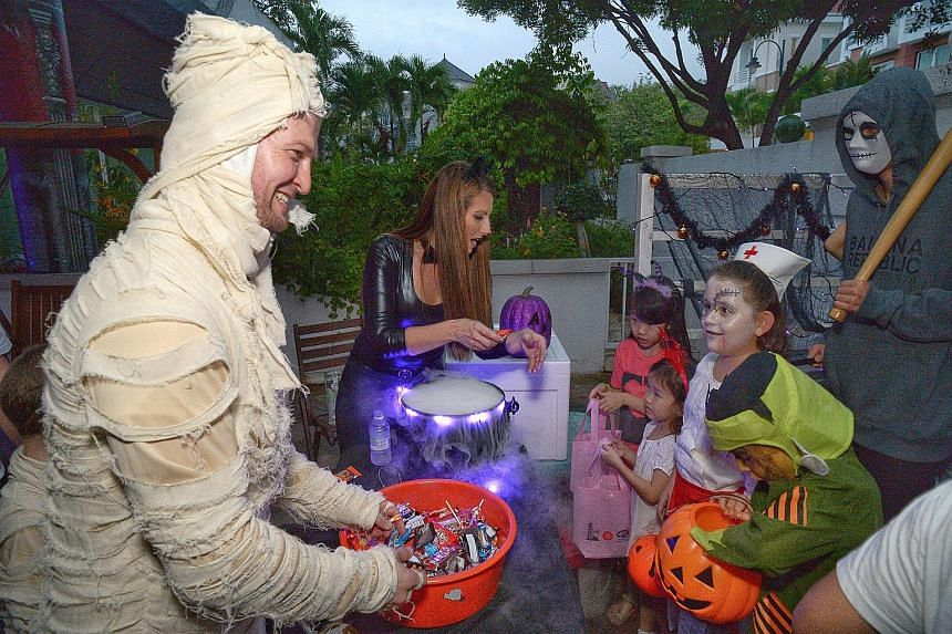 The rain failed to dampen the spirits of these children at Woodgrove last night. Many residents like Mr Jonathan Cabrera (right, in mummy costume), 36, and his wife Jennifer (dressed as Catwoman), 35, gave out treats.