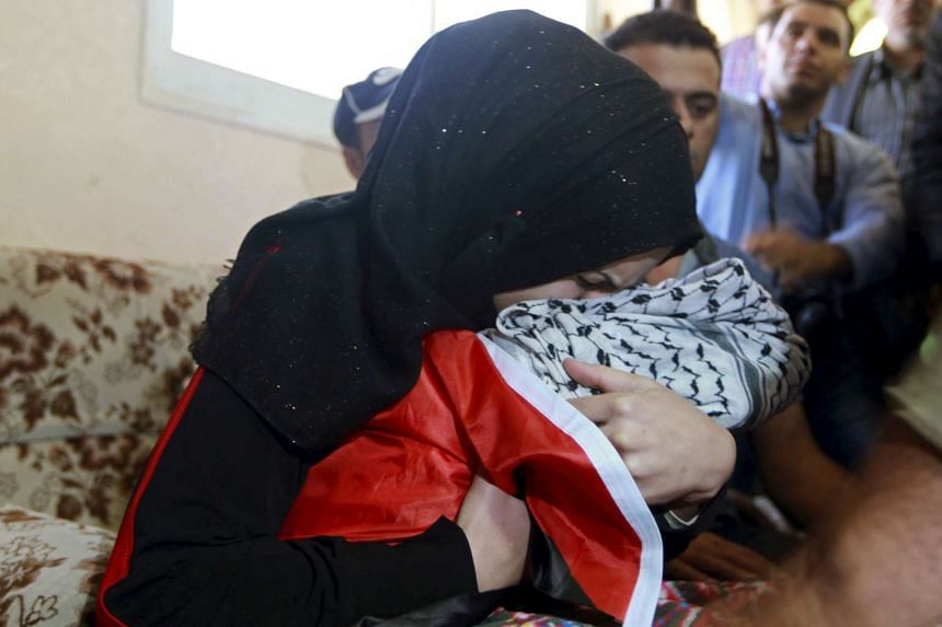 The baby's mother hugs her son's body during his funeral in the West Bank city of Bethlehem.