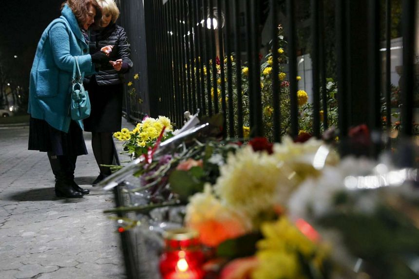 Women light candles for victims of a Russian airliner which crashed in Egypt, outside the Russian embassy in Kiev, Ukraine Oct 31, 2015.