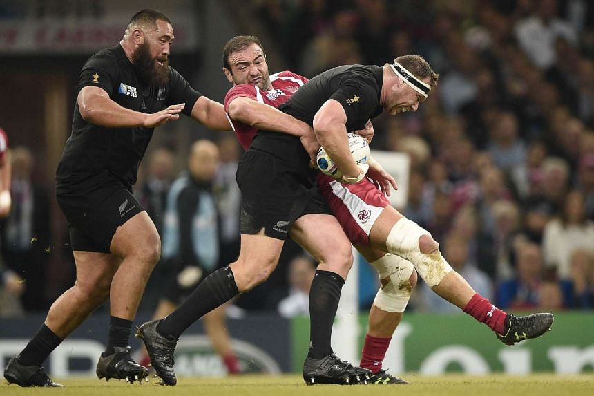 Georgia's flanker and captain Mamuka Gorgodze (centre) tacking New Zealand's prop Wyatt Crockett during their Rugby World Cup 2015 match at the Millennium stadium in Cardiff, south Wales, on October 2, 2015.