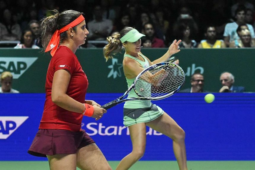 Switzerland's Martina Hingis (back) returns a shot to Spain's Garbine Muguruza and Carla Suarez Navarro as teammate Sania Mirza (front) looks on during their doubles final at the WTA Finals, at the Singapore Indoor Stadium on Nov 1, 2015.