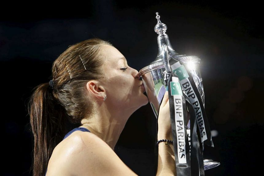Agnieszka Radwanska of Poland kisses her trophy after defeating Petra Kvitova of the Czech Republic in their women's singles finals tennis match of the WTA Finals at the Singapore Indoor Stadium on Nov 1, 2015.