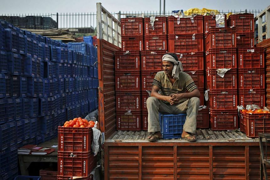 A worker sits on a truck loaded with baskets of tomatoes at a wholesale vegetable market in New Delhi, India, Oct 14, 2015.