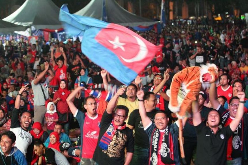 JDT supporters cheering on their team during a football match.