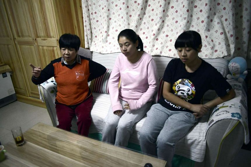 This picture taken on October 31, 2015 shows Li Xue flanked by her sister Li Bin (R) and mother Bai Xiuling (L) as she talks to AFP in their home in Beijing. She was born in Beijing and has lived there all her life. But like millions of others concei