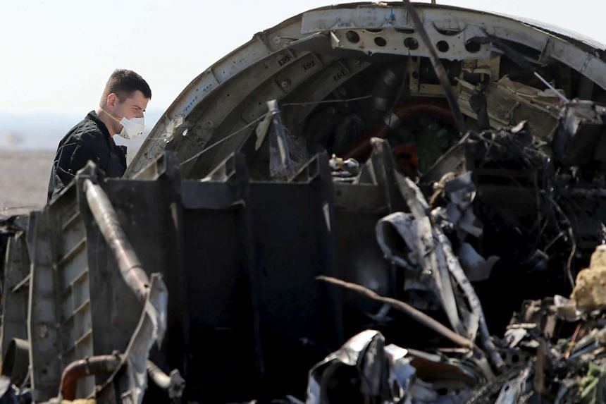 A Russian military investigator standing near the debris of a Russian plane where it crashed in the Hassana area in Arish city, north Egypt, on Nov 1, 2015.