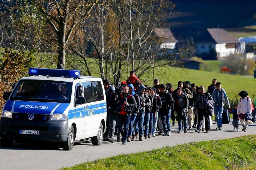 Migrants are escorted by German police to a registration centre, after crossing the Austrian-German border in Wegscheid near Passau, Germany on Nov 1, 2015.