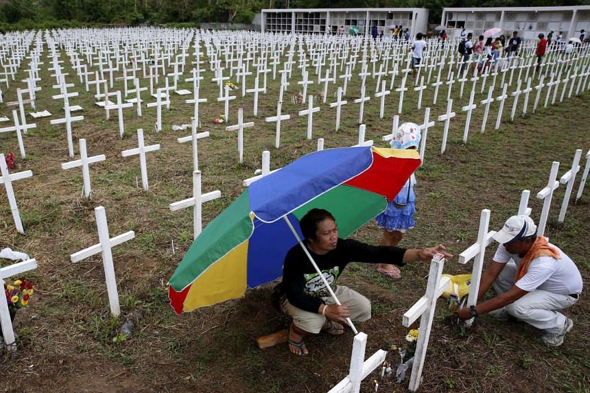 Residents visiting the graves of relatives at a mass grave for Typhoon Haiyan victims on All Saints Day in Tacloban city in the central Philippines, on Nov 1, 2015.