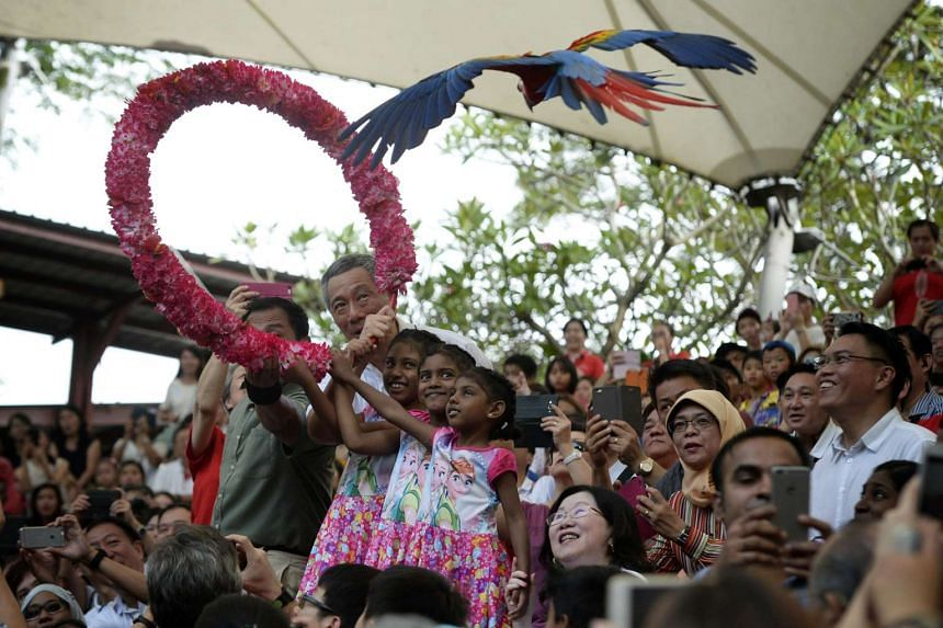 Prime Minister Lee Hsien Loong holding a hoop with sisters (from left), Priyadharshini, Pritika Bernice and Arosaini as a macaw flies through at the Jurong Bird Park during the annual PCF Family Day on Nov 1, 2015.