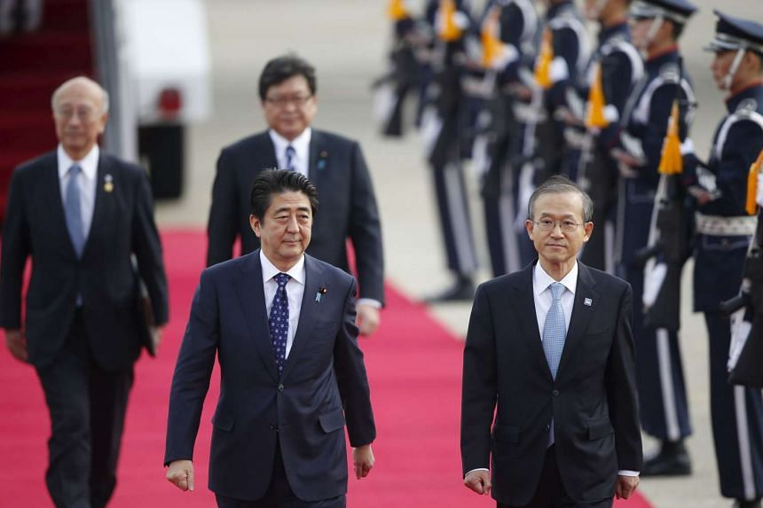Japanese Prime Minister Shinzo Abe (centre) walks with South Korean First Vice Foreign Minister Lim Sung-nam upon his arrival at Seoul Air Base in Seongnam, South Korea.