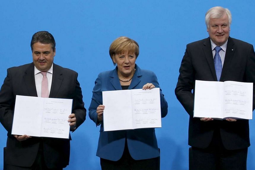 Dr Angela Merkel with Bavarian Premier Horst Seehofer (right) and Social Democratic leader Sigmar Gabriel in a 2013 file photo. The three are scheduled to meet today over the influx of newcomers into Germany.