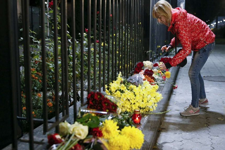 A woman places a candle for victims of a Russian airliner which crashed in Egypt, outside the Russian embassy in Kiev, Ukraine Oct 31, 2015.