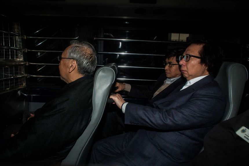 Rafael Hui (left) and Thomas Kwok (right) in a prison van in Hong Kong on Dec 22, 2014.