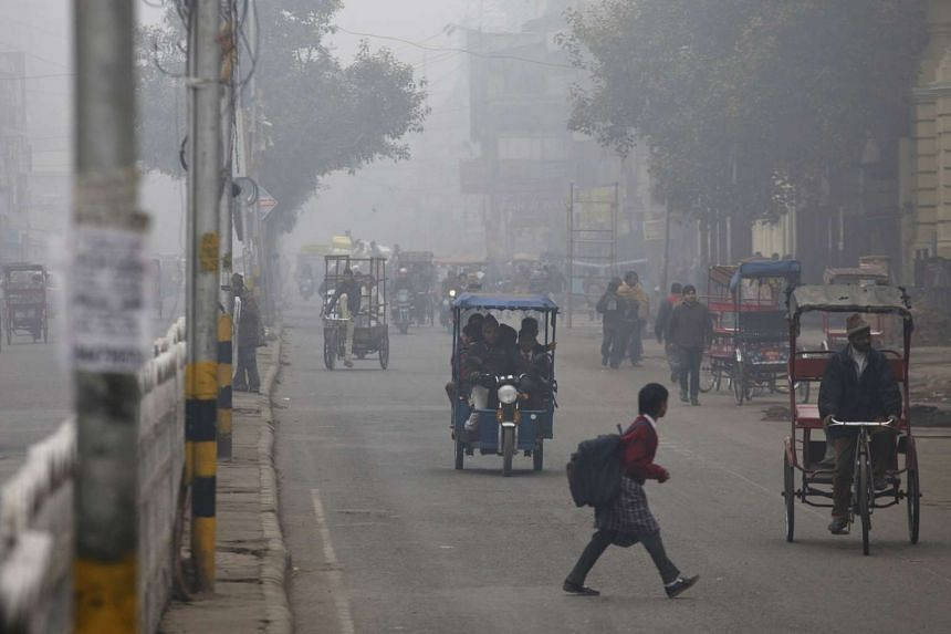 Traffic on a street in New Delhi moves through haze caused by air pollution, on Jan 20, 2014.