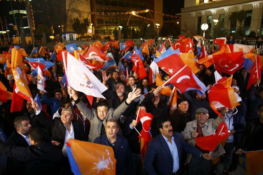 People waving flags outside the AK Party headquarters in Ankara, Turkey on Nov 1, 2015.