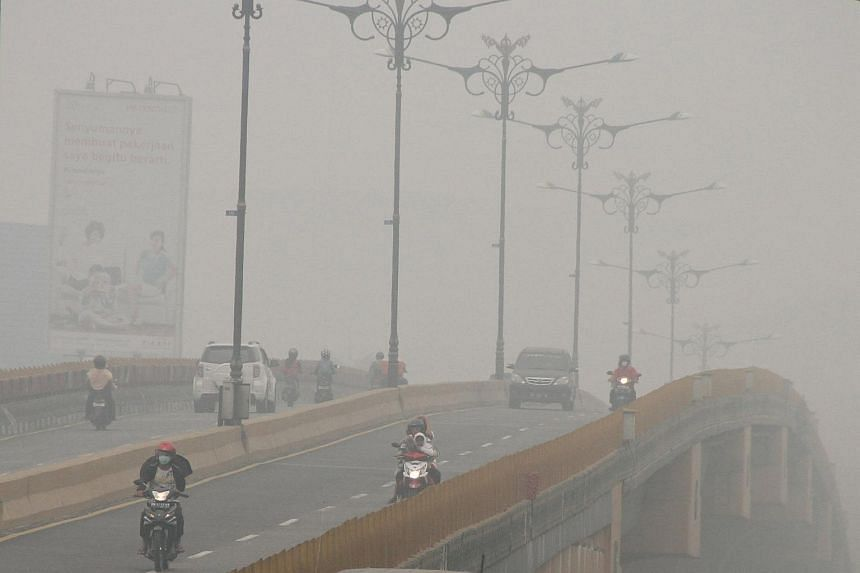 Cars and motorcycles are seen on a bridge as haze shrouds Pekanbaru, in Indonesia's Riau province, on Sept 30, 2015.