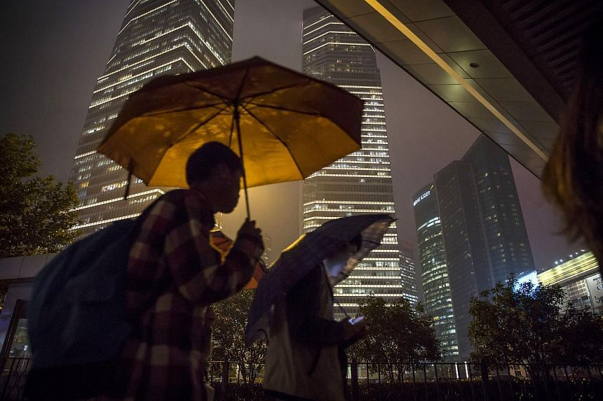 Pedestrians walking past buildings illuminated at night in the Lujiazui district of Shanghai, China.