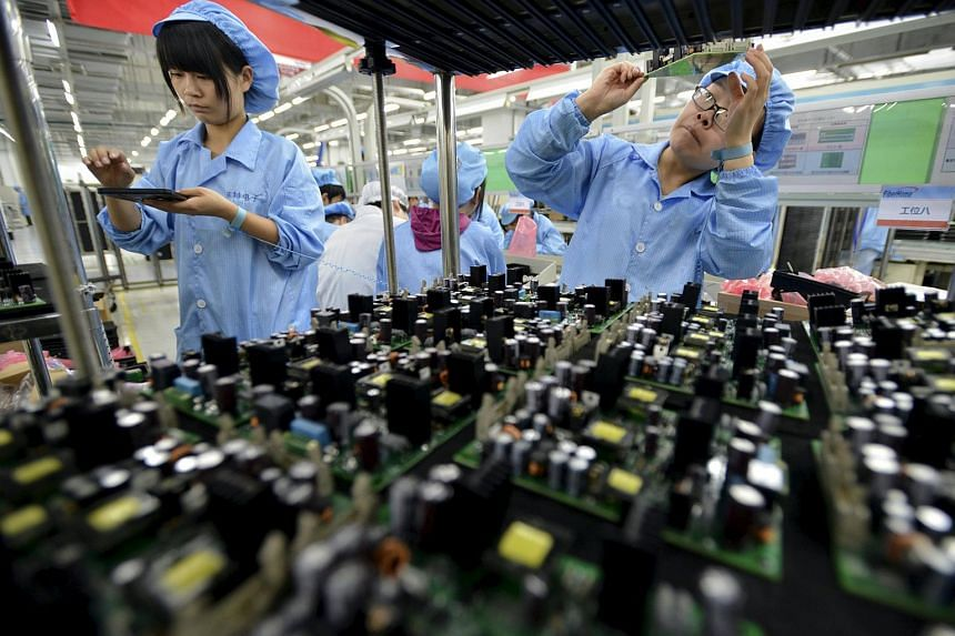 Employees work at a production line of electronic panels at a FiberHome Technologies factory in Wuhan in China's Hubei province.